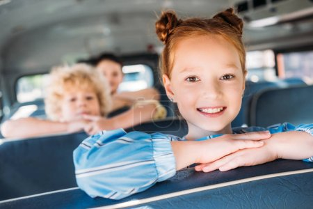 close-up portrait of smiling little schoolgirl riding on school bus with classmates behind