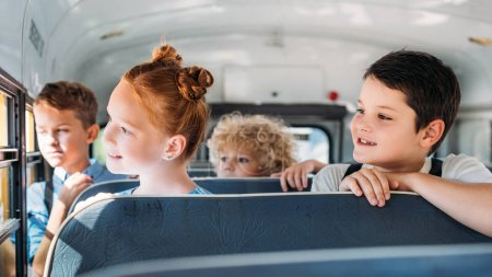 group of schoolchildren riding on school bus and looking through window