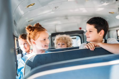 group of happy little pupils riding on school bus