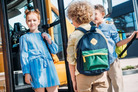 group of pupils standing near school bus and talking