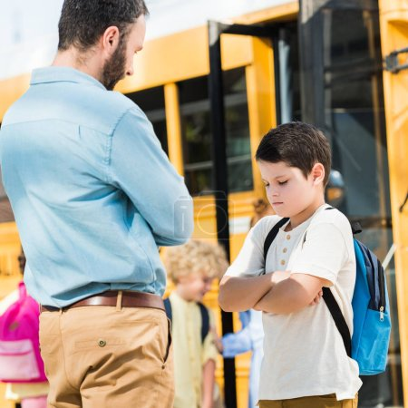 angry father preaching his depressed son in front of school bus
