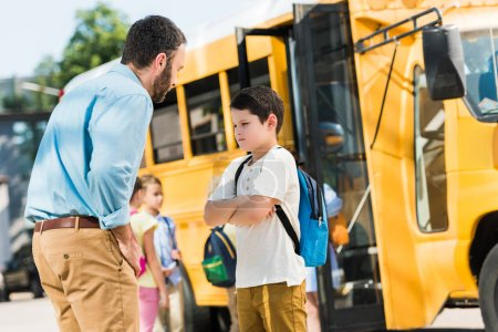 angry father preaching his son in front of school bus