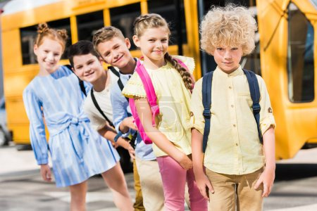 group of adorable pupils looking at camera while standing in row in front of school bus