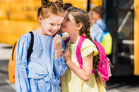 cute little schoolgirls gossiping in front of school bus