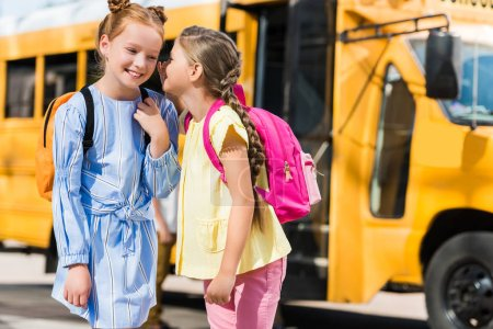happy little schoolgirls gossiping in front of school bus
