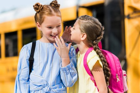 adorable little schoolgirls gossiping in front of school bus