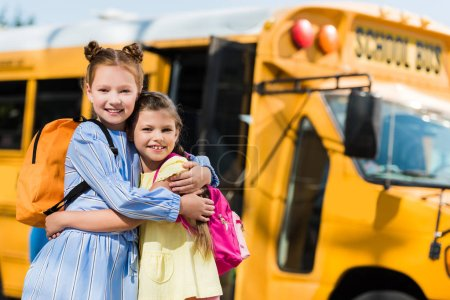 happy little schoolgirls embracing in front of school bus and lookin at camera