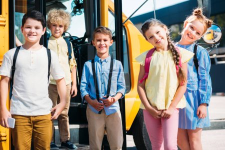Photo for Group of happy pupils looking at camera in front of school bus - Royalty Free Image