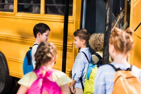 group of adorable schoolchildren chatting near school bus