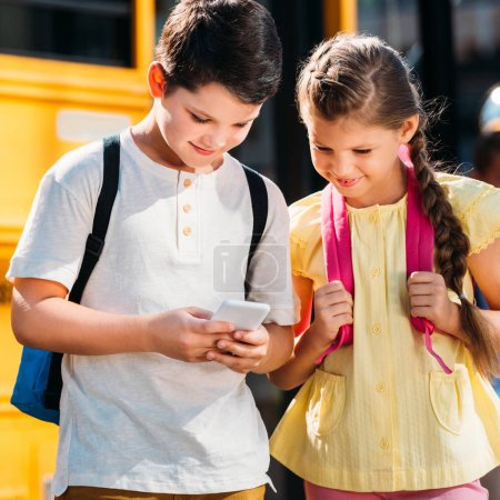 happy little scholars using smartphone together in front of school bus