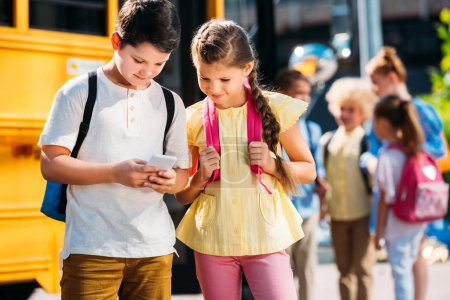 schoolgirl and schoolboy using smartphone together in front of school bus with classmates