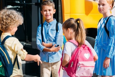 group of adorable pupils chatting near school bus