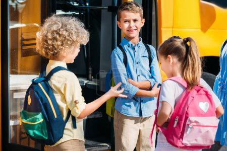 adorable pupils chatting near school bus