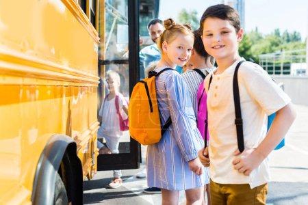 alumnos poco felizes entrar en autobús de la escuela con compañeros de clase