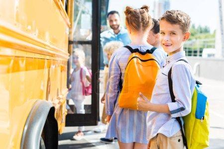 smiling little schoolboy entering school bus with classmates while teacher standing near door