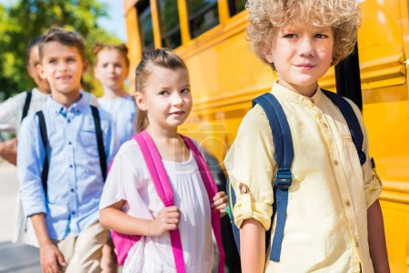 group of adorable classmates near school bus