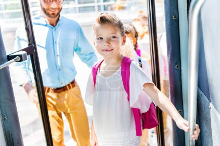 beautiful little schoolgirl entering school bus with teacher and classmates on background