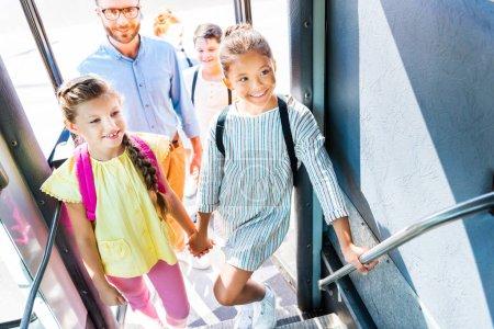 Grupo de alumnos entrar en autobús de la escuela con el maestro