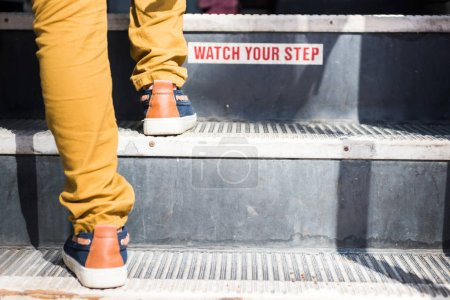 "cropped shot of child going upstairs in bus with ""watch your step"" sign"