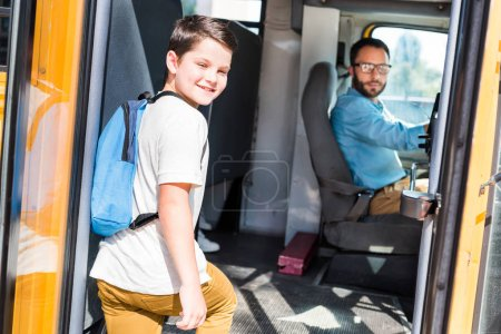 handsome school bus driver and schoolboy looking at camera