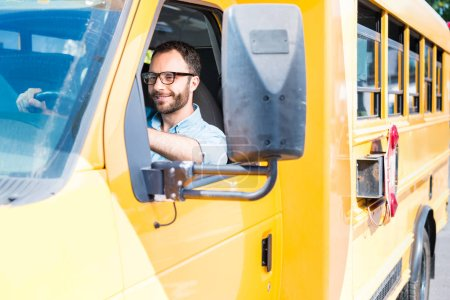 Photo for Handsome school bus driver smiling and driving - Royalty Free Image