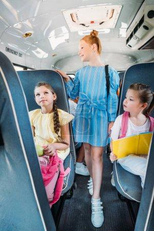 group of adorable schoolgirls riding on school bus