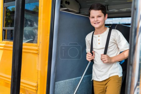 smiling schoolboy with backpack standing in school bus and looking at camera
