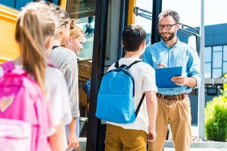 alumnos entrar en autobús escolar mientras la maestra escribe en el portapapeles