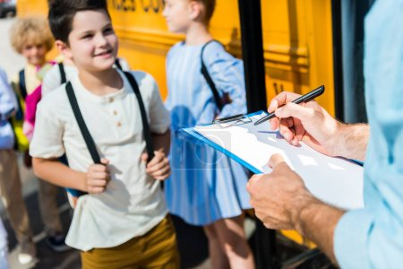 cropped shot of teacher writing in list on clipboard while pupils entering at school bus blurred on background