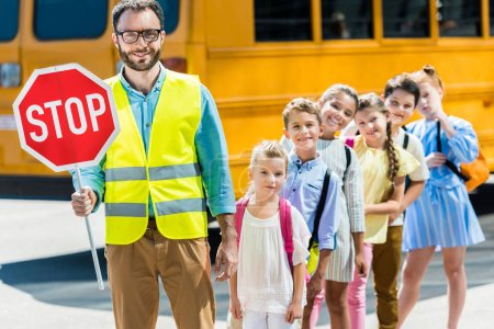 Photo for Miling traffic guard with scholars looking at camera in front of school bus - Royalty Free Image