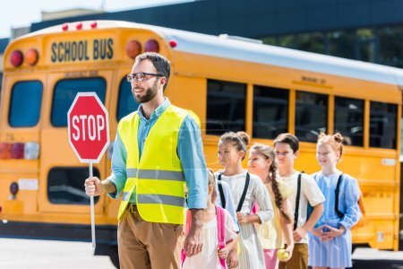 traffic guard crossing road with schoolchildren in front of school bus