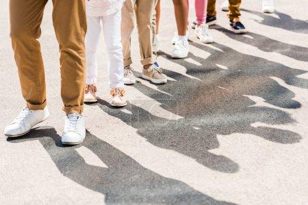 Foto de Recortado tiro de un adulto y niños en varios zapatos y pantalones de pie en fila - Imagen libre de derechos