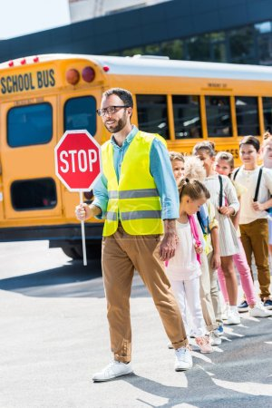 traffic guard crossing road with happy pupils in front of school bus