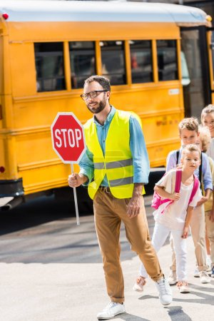 happy traffic guard crossing road with pupils in front of school bus