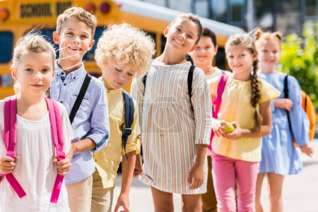 Photo for Group of happy pupils standing in row in front of school bus - Royalty Free Image