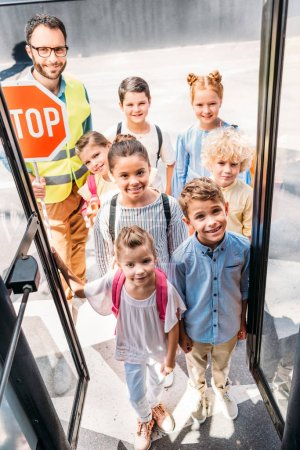 view from school bus at group of happy choolchildren with traffic guard looking at camera