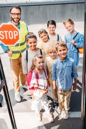view from school bus at group of schoolchildren with traffic guard looking at camera
