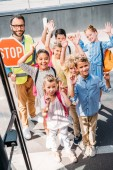 view from school bus at group of scholars with traffic guard looking at camera and waving