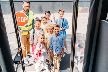 view from school bus at group of pupils with traffic guard looking at camera