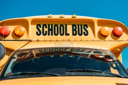 Photo for Close-up shot of school bus with inscription in front of blue sky - Royalty Free Image