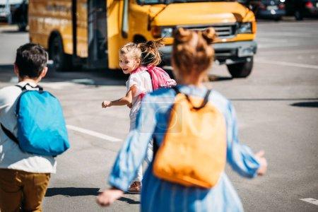 rear view of happy schoolchildren running to school bus