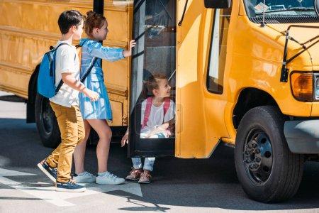 scholars relaxing near school bus on parking