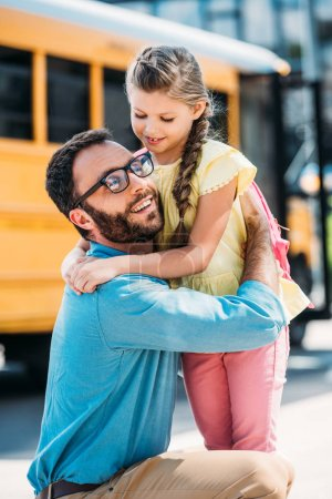 happy father embracing his little daughter in front of school bus