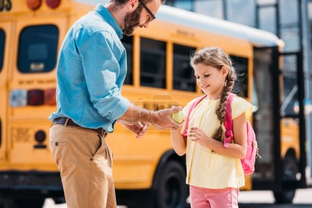 father giving fresh green apple to daughter in front of school bus