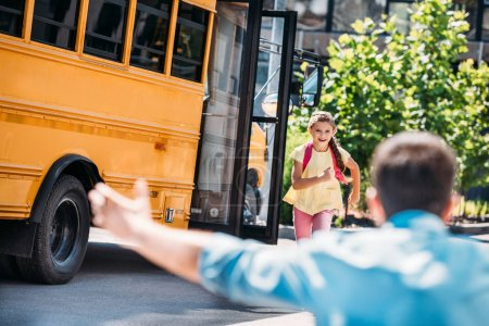 rear view of father with open arms waiting for adorable little daughter while she running from school bus