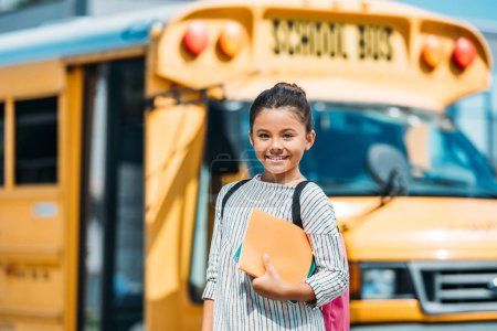 happy little schoolgirl with notebooks looking at camera in front of school bus