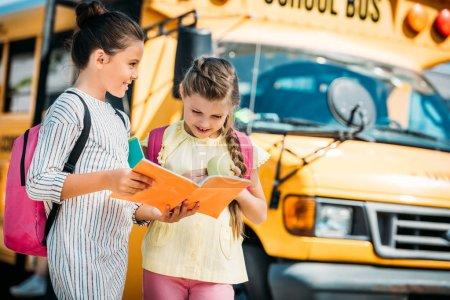 adorable little schoolgirls with notebook discussing homework in front of school bus