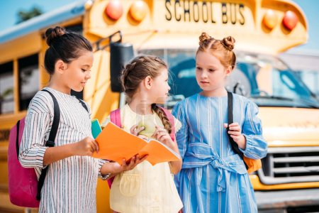group of adorable little schoolgirls with notebook talking in front of school bus