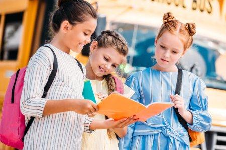 group of little schoolgirls looking at notebook in front of school bus