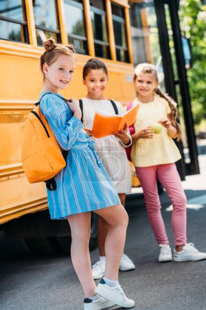 happy little schoolgirls with notebook looking at camera in front of school bus